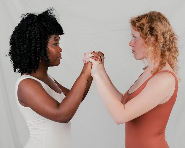 Um, africano, e, loiro, mulheres jovens, ficar, cara enfrentar, segurar, um, outro, mão