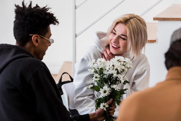 Um, africano, homem jovem, dar, flores brancas, buquê, para, dela, sorrindo, namorada