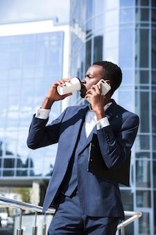 Um, africano, homem negócios fica, frente, edifício escritório, falando telefone móvel, café bebendo