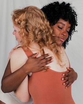 Um, africano, mulher jovem, abraçando, dela, loiro, amigo feminino