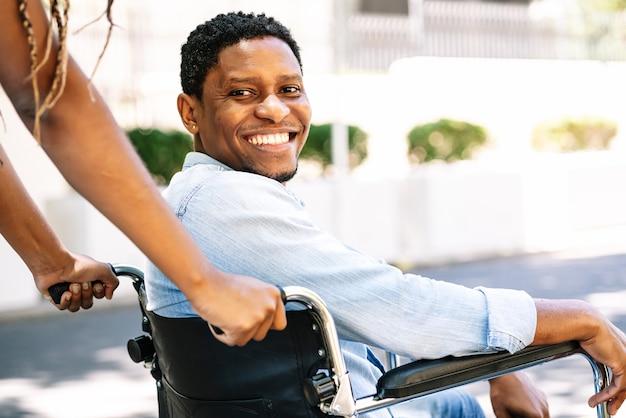 Um afro-americano em uma cadeira de rodas, sorrindo e olhando para a câmera enquanto sua namorada o empurra.