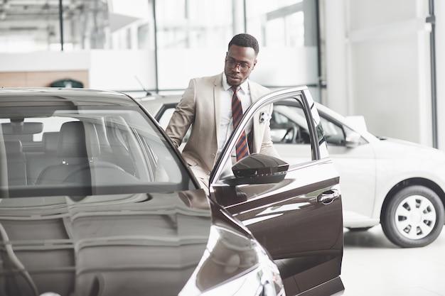 Um afro-americano inspeciona o carro na concessionária. boa pechincha.