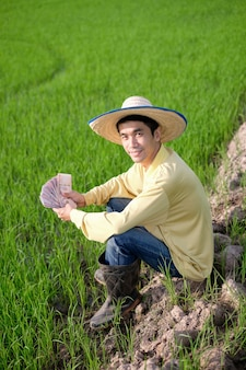 Um agricultor asiático usa uma camisa amarela sentado em um campo de arroz com as notas tailandesas sorrindo.