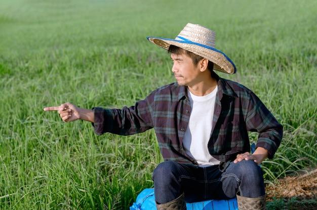 Um agricultor com uma camisa listrada está sentado apontando o dedo no trabalho no meio de um campo.