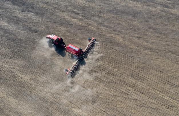 Um agricultor em um trator prepara a terra com um cultivador de semeadura como parte do trabalho de pré-semeadura no início da temporada agrícola de primavera em terras agrícolas.