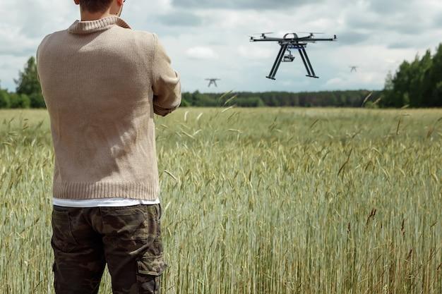 Um agricultor gerencia um drone sobre terras agrícolas.