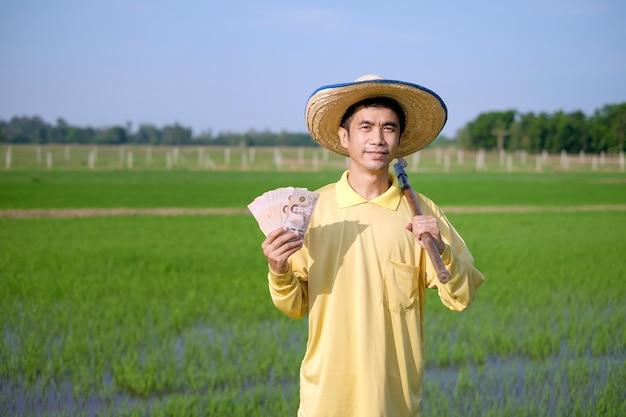 Um agricultor vestindo uma camisa amarela de mangas compridas está segurando notas em um campo verde.