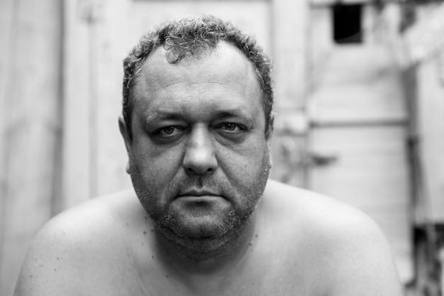 Um alcoólatra adulto com a barba por fazer e o torso nu no pátio de uma casa na aldeia. fechar-se. foto em preto e branco.