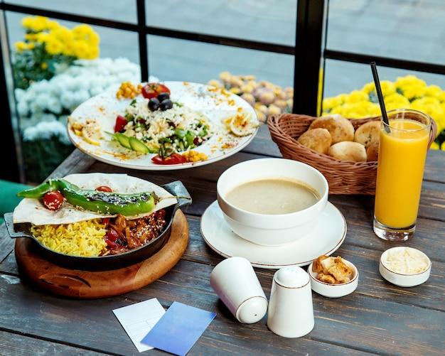 Um almoço com frango teriyaki, salada verde, pão de cogumelos e suco de laranja