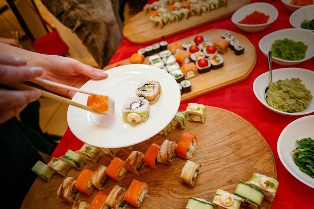Um almoço de sushi, sushi no prato, mãos com pauzinhos