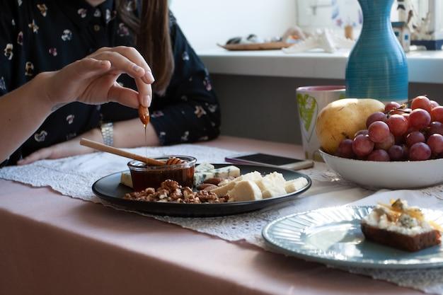 Um almoço gourmet: um prato preto de aperitivos numa toalha de mesa branca: nozes, amêndoas, queijo