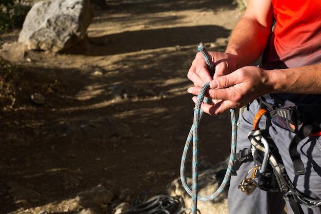 Um alpinista do sexo masculino dá um nó de segurança oito no arnês antes de subir a pista. equipamento de escalada: corda, tracção rápida, dispositivo de segurança, arnês. turismo esportivo de montanha, estilo de vida ativo, esportes radicais