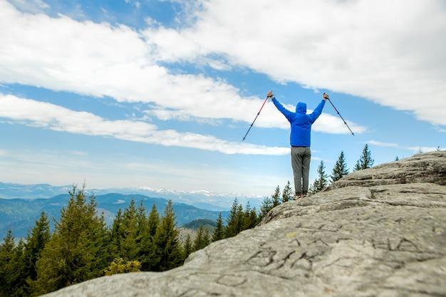 Um alpinista está alto nas montanhas contra o céu, comemorando a vitória, levantando as mãos para cima