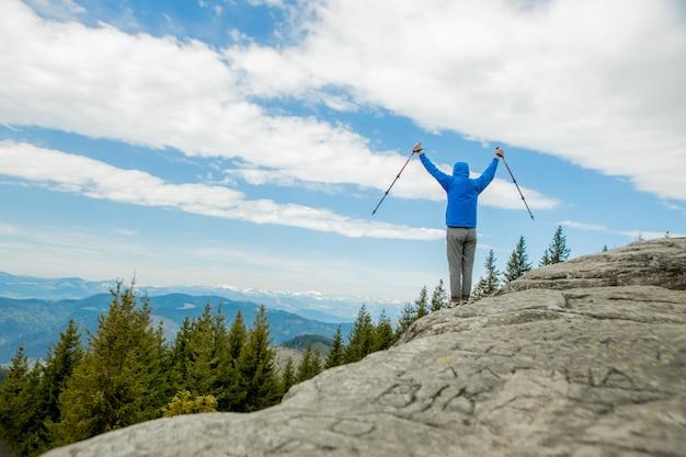 Um alpinista está alto nas montanhas contra o céu, comemorando a vitória, levantando as mãos.