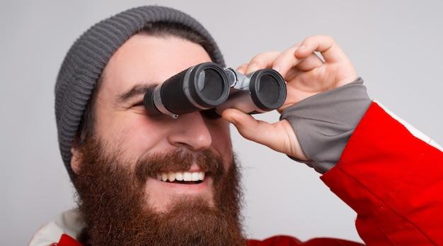 Um alpinista jovem e barbudo olhando através de um binóculo e sorrindo.
