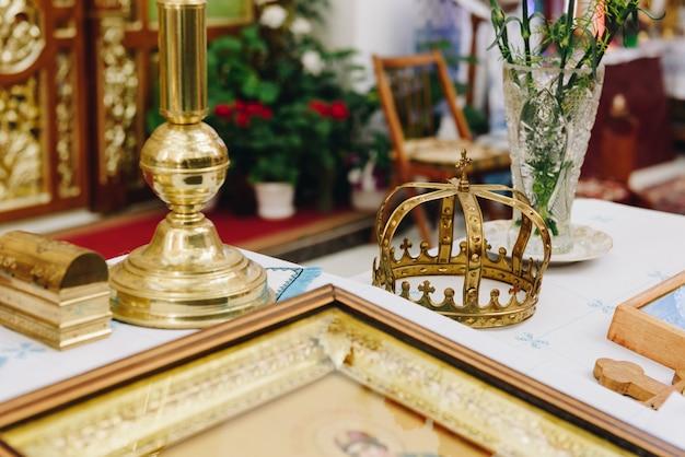 Um altar com ícones de casamento e close de coroa de casamento