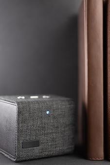 Um alto-falante portátil bluetooth está em uma prateleira.