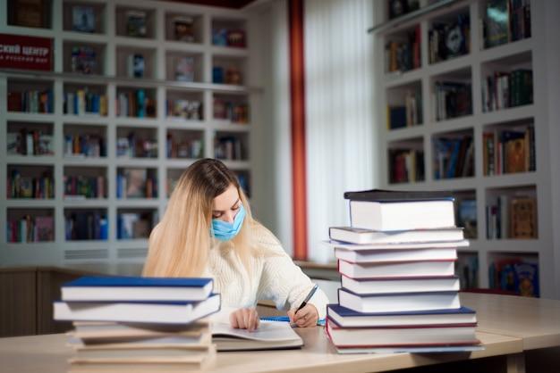 Um aluno cansado com uma máscara protetora para o rosto estudando na biblioteca da escola.