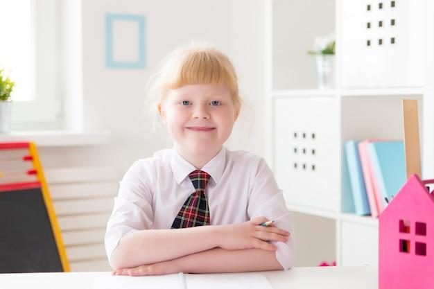 Um aluno da primeira série está sentado em uma mesa