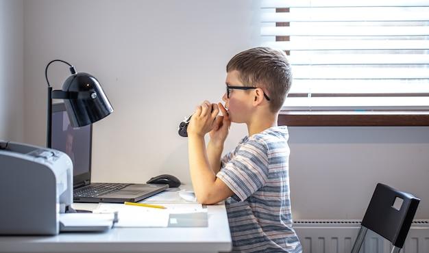 Um aluno do ensino fundamental senta-se em uma mesa em frente a um laptop e se comunica por meio de um link de vídeo online em casa.
