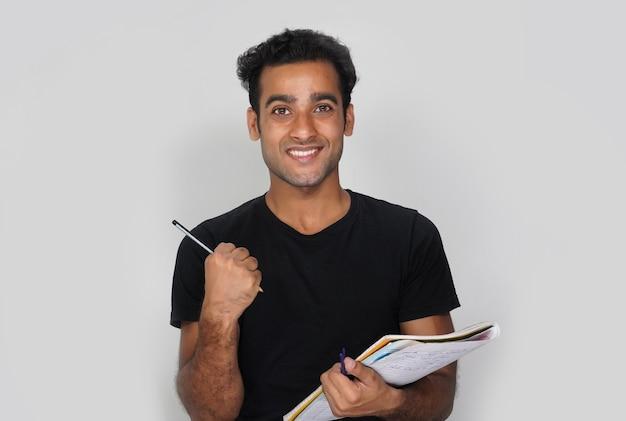 Um aluno feliz com livros e lápis - conceito de educação