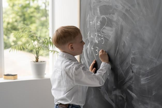 Um aluno moderno na sala de aula escreve exemplos de matemática no quadro-negro.