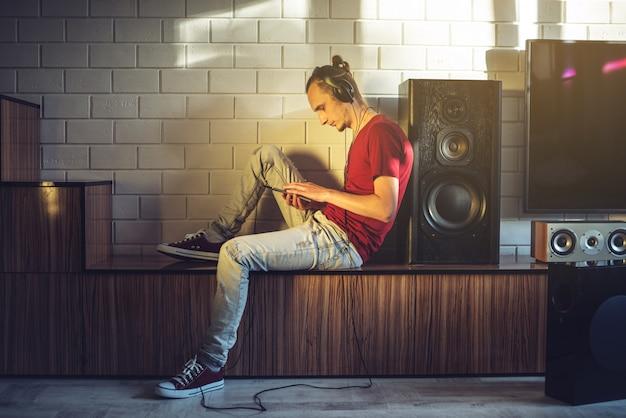 Um amante de música ouve música com fones de ouvido com um telefone celular na mídia e alto-falantes grandes.