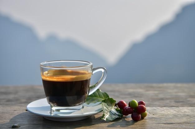 Um americano em uma xícara de café transparente com vista para a montanha de fundo