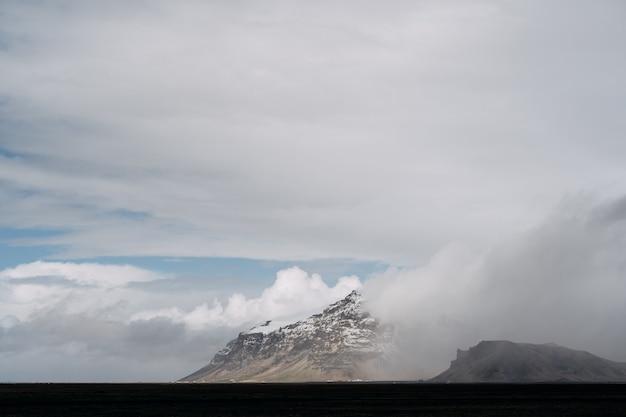Um amplo campo de grama seca e amarela e uma montanha à distância com um pico coberto de neve contra um