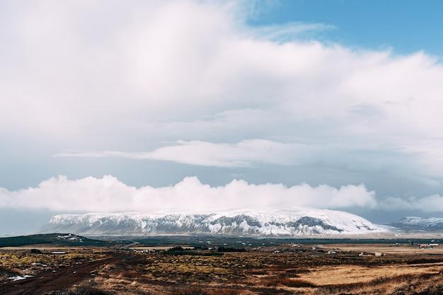 Um amplo campo de grama seca e uma montanha ao longe com um pico coberto de neve