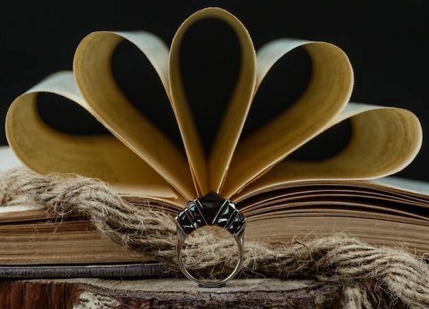 Um anel com pedras cor de vinho na frente do livro aberto, estilo rústico