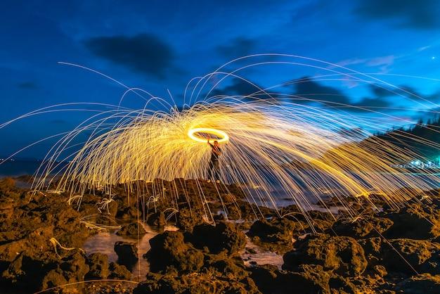 Um anel de lãs de aço de giro do fogo na rocha e na praia.