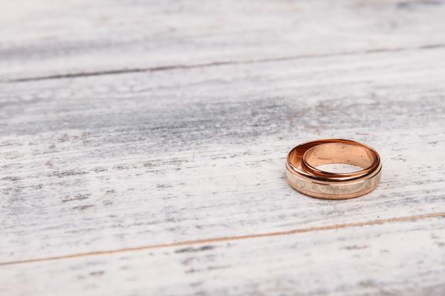 Um anel de ouro em madeira branca.