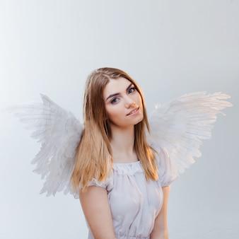 Um anjo do céu. jovem loira maravilhosa à imagem de um anjo com asas brancas. close-up retrato