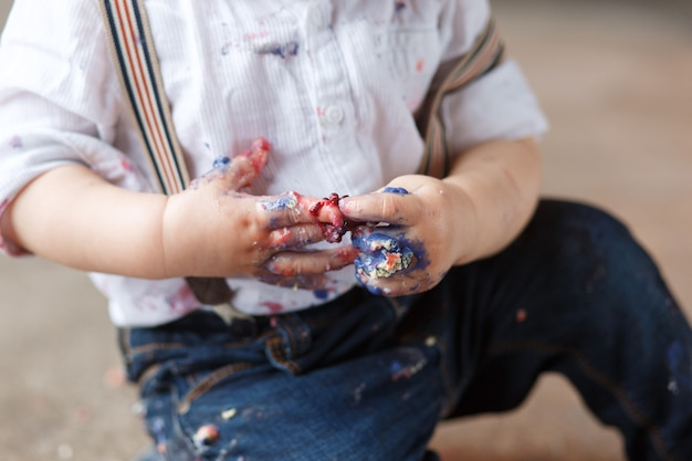 Um ano de idade garoto depois de comer uma fatia de aniversário esmagar o bolo sozinho se sujar.
