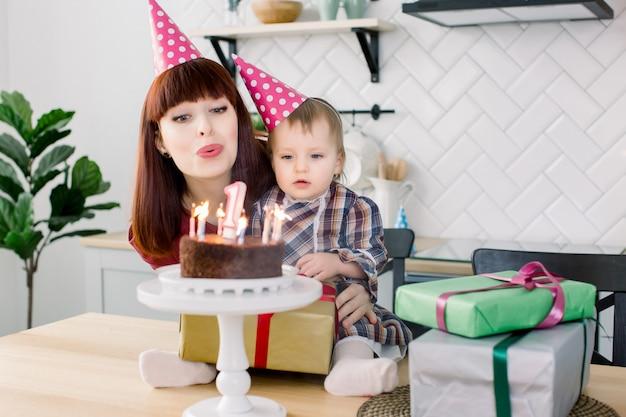Um ano de idade menina sopra velinhas no bolo em seu aniversário com sua mãe feliz.
