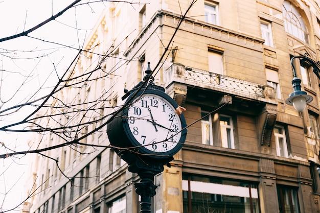 Um antigo posto de rua com um relógio nas ruas de budapeste
