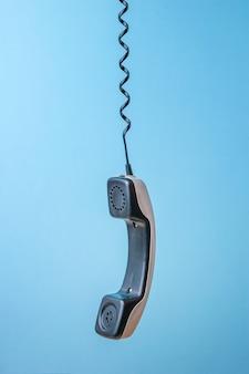 Um aparelho de telefone retro cinza suspenso por um fio em um fundo azul.