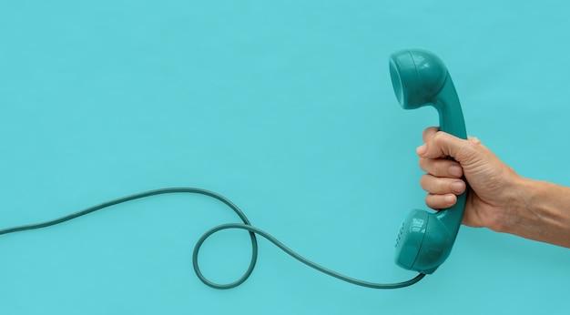 Um aparelho de telefone vintage azul esverdeado com uma mão e fundo azul esverdeado.