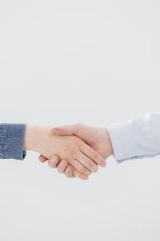 Um aperto de mão de duas pessoas, um homem e uma mulher, parceiros de negócios cumprimentando