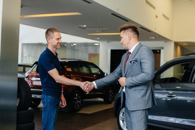 Um aperto de mão firme depois de comprar um carro novo em uma jovem concessionária de carros familiares