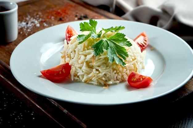 Um apetitoso acompanhamento oriental é o arroz com açafrão, servido em um prato branco sobre uma bandeja de madeira. mesa escura