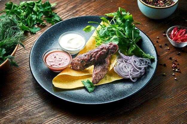 Um apetitoso prato da culinária turca - kebab de carne picada com pão sírio, coentro, cebola e molhos, servido em um prato azul sobre uma mesa de madeira. comida do restaurante. vista de perto