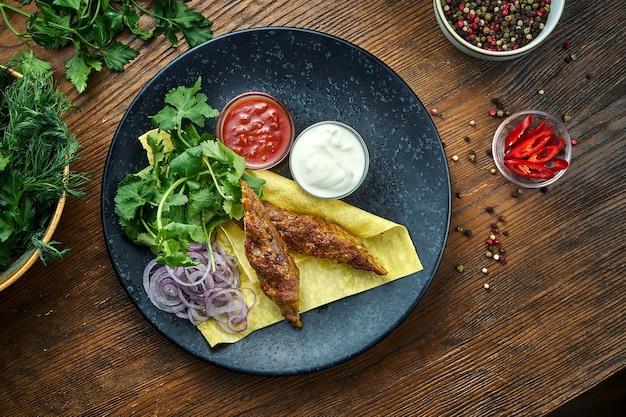 Um apetitoso prato da culinária turca - kebab de frango de carne picada com pão sírio, coentro, cebola e molhos, servido em um prato azul sobre uma mesa de madeira. comida do restaurante. vista de perto