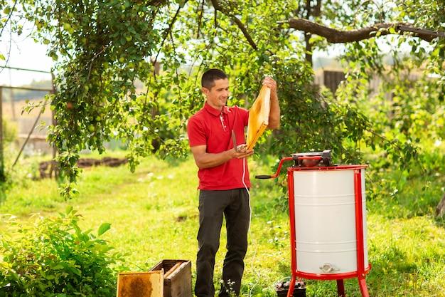 Um apicultor em uma tampa protetora lança no trabalho um extrator de mel na fazenda de abelhas