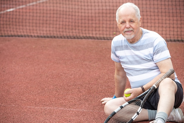 Um aposentado ativo, retrato de homem sênior jogando tênis no exterior, esportes aposentado, conceito de esporte