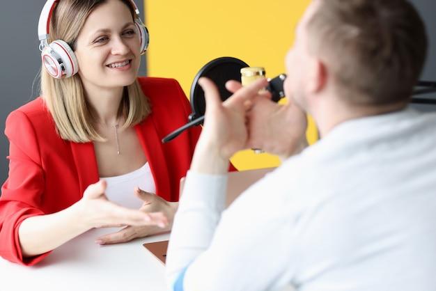 Um apresentador de rádio de conteúdo atraente entrevista um convidado em um estúdio que trabalha como apresentador no rádio