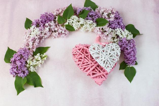 Um arco de lilás e dois corações de vime
