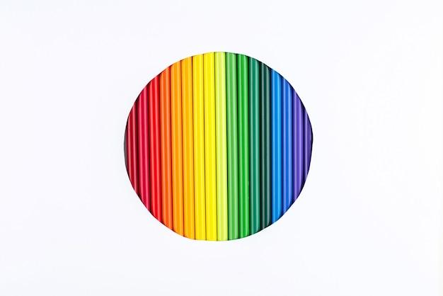 Um arco-íris de lápis em um círculo recortado em um fundo de papel branco.