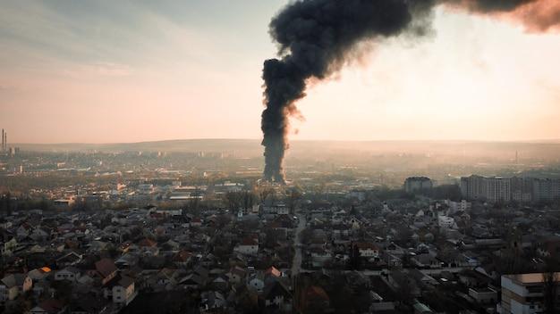 Um armazém em chamas com uma alta coluna negra de fumaça no setor residencial de chisinau, moldávia